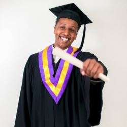 Photo of graduate holding diploma out and smiling