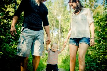 Parents walking with a toddler in the forest