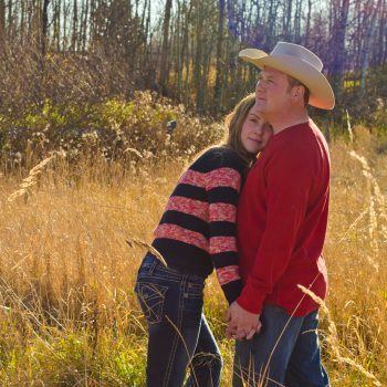 Woman leans on a man who is wearing a cowboy hat on an acreage in Alberta