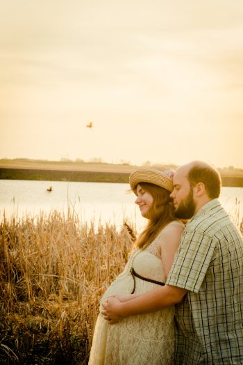 Couple looking forward to their baby by the lake