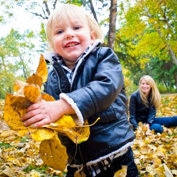 Young boy throwing leaves while Mom watches at Emily Murphy Park