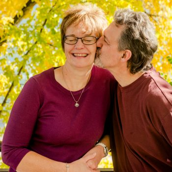 Candid photo of man kissing his wife's cheek in fall