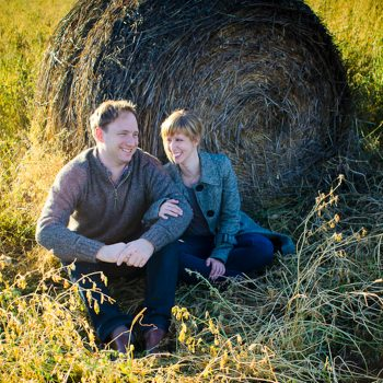 Couple leans against a hay bale in a field in St. Albert's Lacombe Lake Park