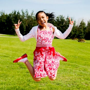 Asian girl makes hand signs as she jumps
