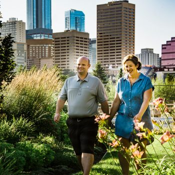Couple walks holding hands with a backdrop of the Edmonton city skyline