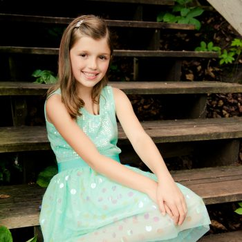 Young girl on stairs in green dress at Emily Murphy Park