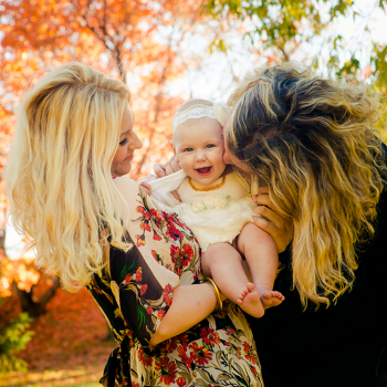Dad kissing his baby daughter while mom looks on, Fall Family Photos at Emily Murphy Park