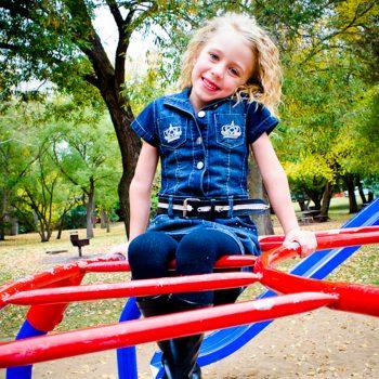 Girl on playground equipment at Emily Murphy Park