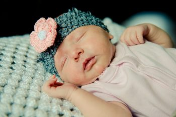 Baby girl in a pink onesie with a crocheted headband