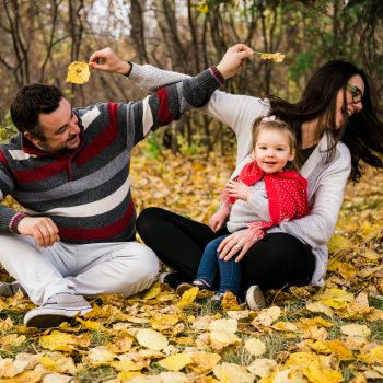 Dad and Mom pester each other with leaves in Gold Bar Park while baby daughter looks on