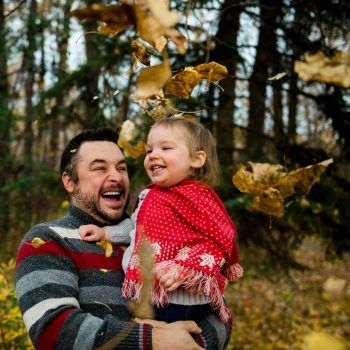Dad and baby daughter in a shower of leaves in Gold Bar Park