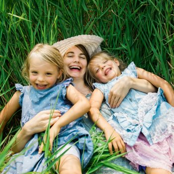 Mom and two daughters laughing in the grasses in Martensville