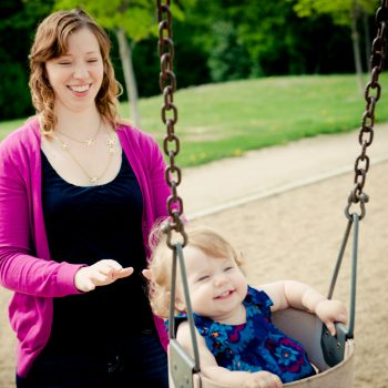 Mom pushing baby daughter on a swing at the park
