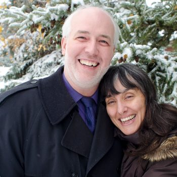 Photo of Couple in front of a snowy Christmas tree