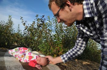 Dad touching Baby's head on a picnic blanket outdoors
