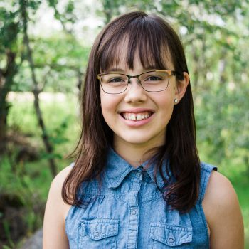 Pre-teen girl with glasses in a forest on an acreage