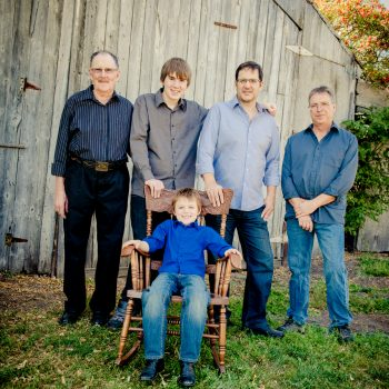 All the men in the family on the acreage beside the barn