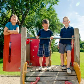 Siblings on a playground structure in Saskatoon