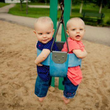 Twin baby girls in a swing