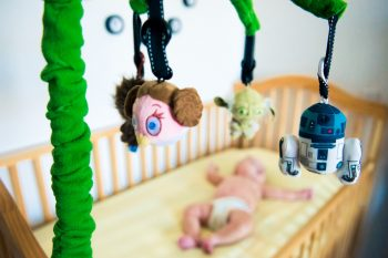 Star wars themed baby mobile with the baby and crib in the background