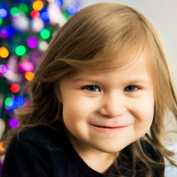 Young girl with christmas tree lights behind her for family portraits